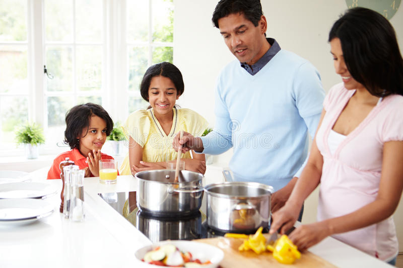 Indian Family Cooking Meal At Home. Talking To Each Other royalty free stock image