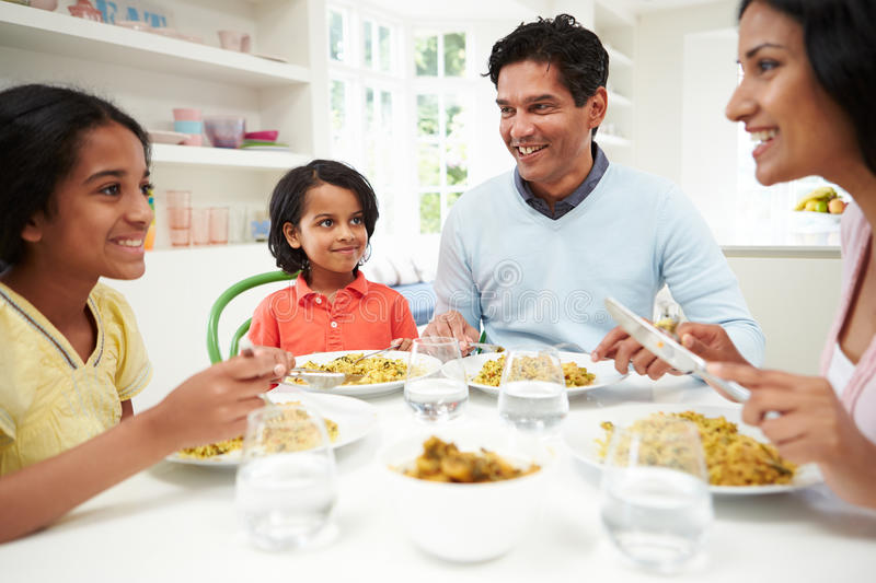 Indian Family Eating Meal At Home. In Kitchen Smiling At Each Other stock photo