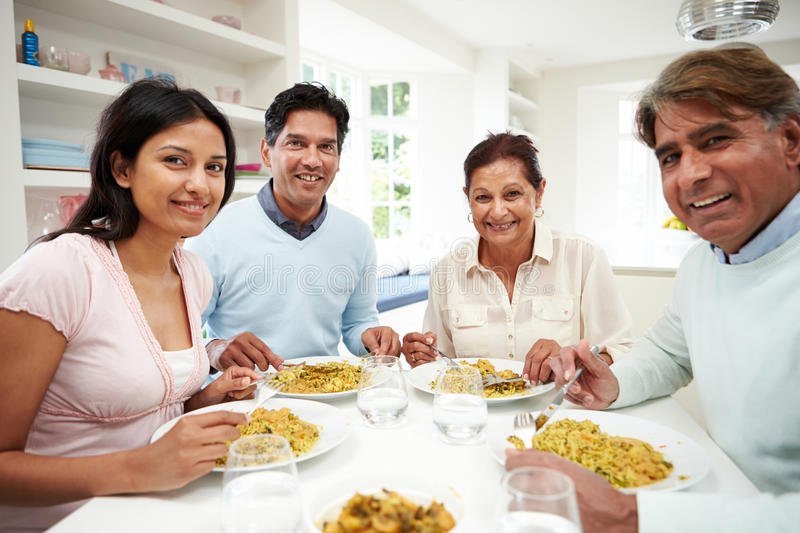 Indian Family Eating Meal At Home. Looking To Camera Smiling stock photos