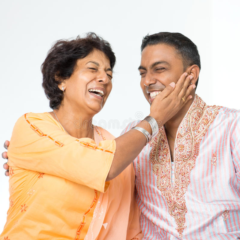 Indian family fun talking. Portrait of happy Indian family having fun conversation at home. Mature 50s Indian mother and her 30s grown son royalty free stock photos
