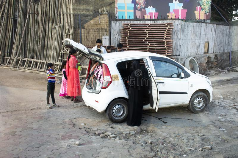 Indian family people mother father child keeping and pick up object to inside eco car at beside road in New Delhi, India stock image