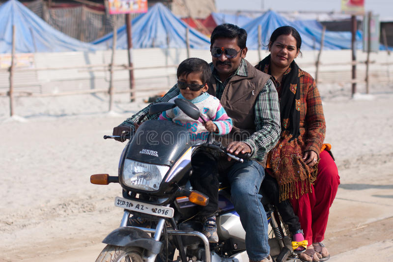 Indian family rides a motorbike. On a holiday during hindu festival Kumbh Mela on January 28, 2013 in Allahabad, India. Kumbh Mela is the largest single royalty free stock photos