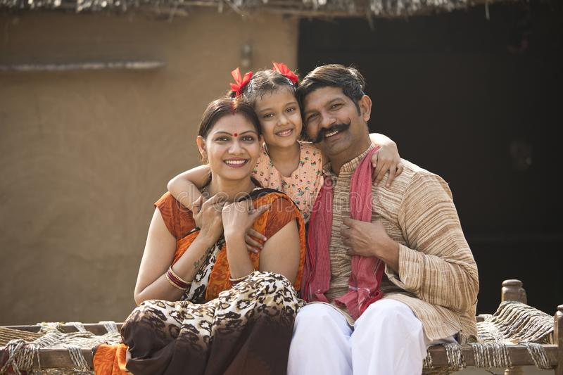 Indian family sitting on traditional bed in village royalty free stock photo