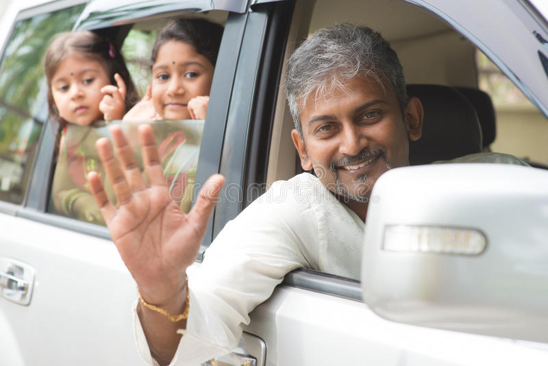 Indian family waving hands in car stock photos
