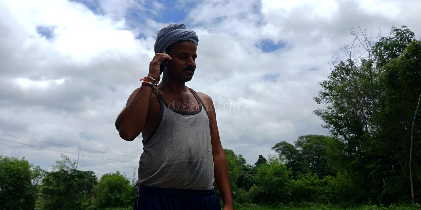 An indian farmer talking to mobile phone in the forest area. Shipyard, lady, seating, animals, pot, villager, teen, operating, laptop, computer, corridor stock images