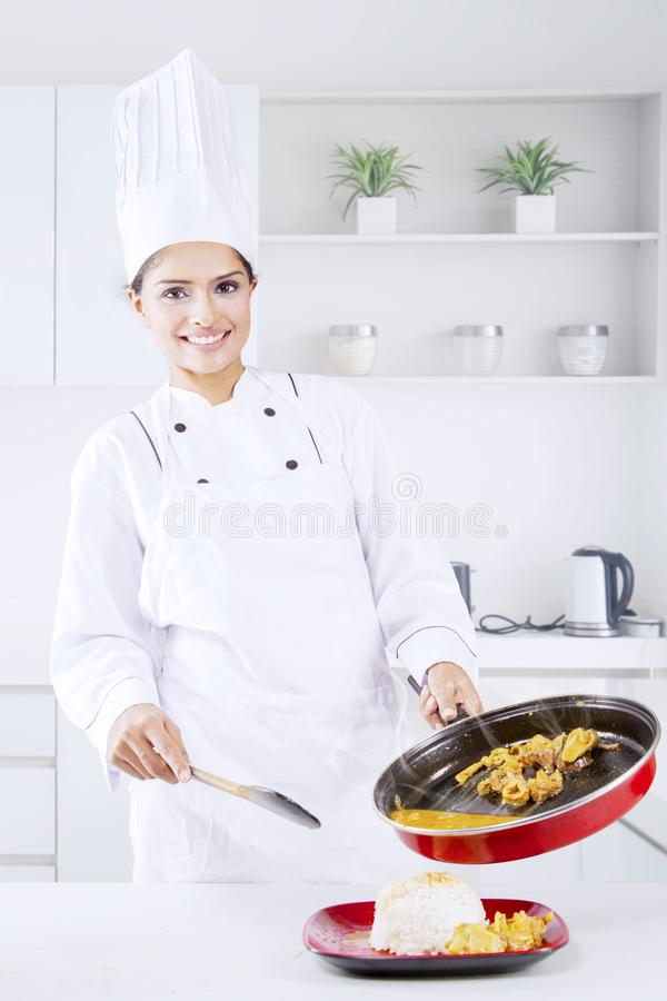 Indian female chef pours tripe soup into a plate. Indian female chef pouring tripe soup into a plate with white rice while standing in the kitchen stock images