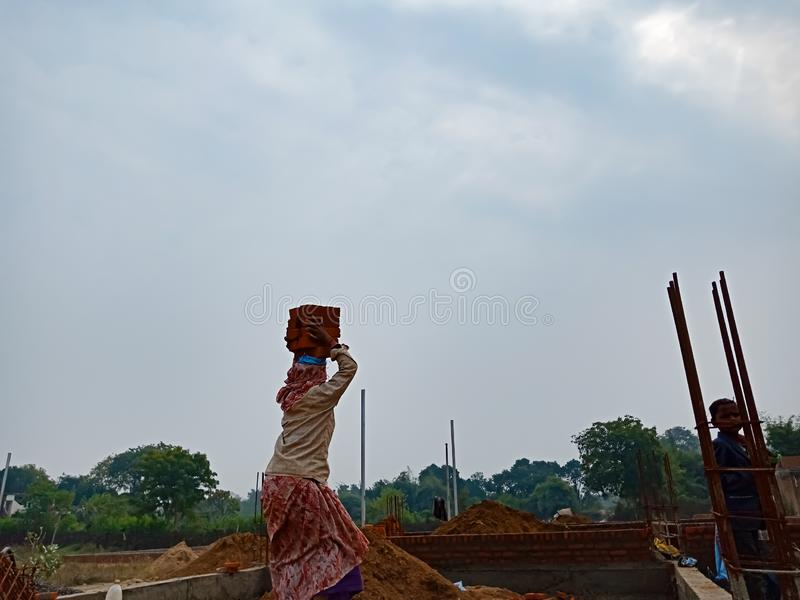 an indian female labour transporting building materials on head during construction in india dec 2019 stock image