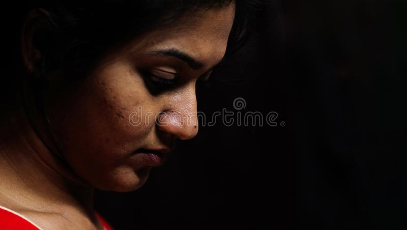 An indian female staring down in worry and depression in black background with selective focus on nose royalty free stock photos