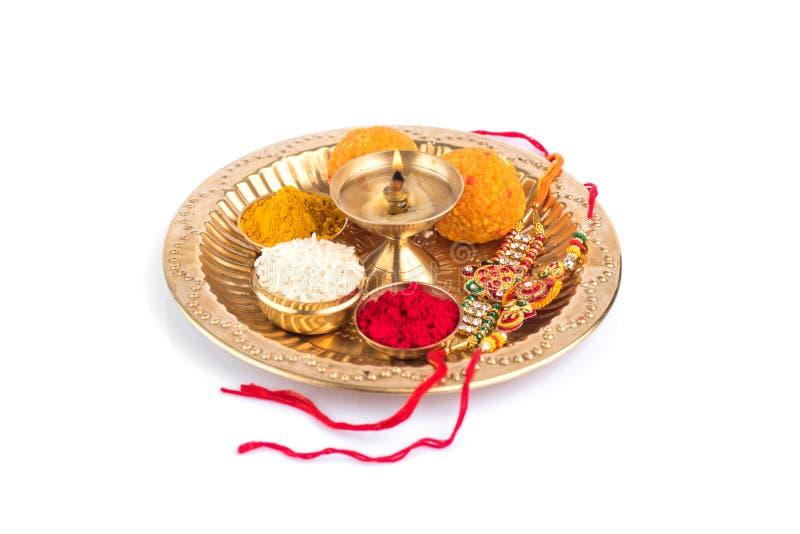 Indian Festival Raksha Bandhan with Rakhi and rice grains, kumkum, sweets and Diya on a worship plate. Indian Festival: Rakhi with rice grains, kumkum, sweets royalty free stock photos
