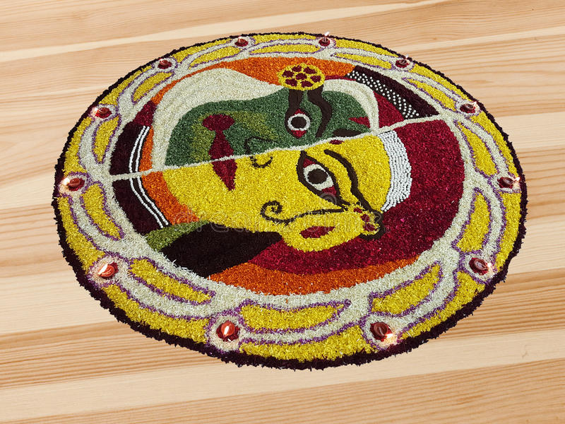 Indian festival traditional floral design art with colorful flower petals. On a wooden floor. The design includes diyas or lamps on the circumference of the royalty free stock photography
