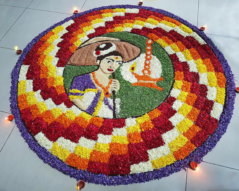Indian festival traditional floral design art with colorful flower petals. On a wooden floor. The design includes diyas or lamps on the circumference of the royalty free stock image
