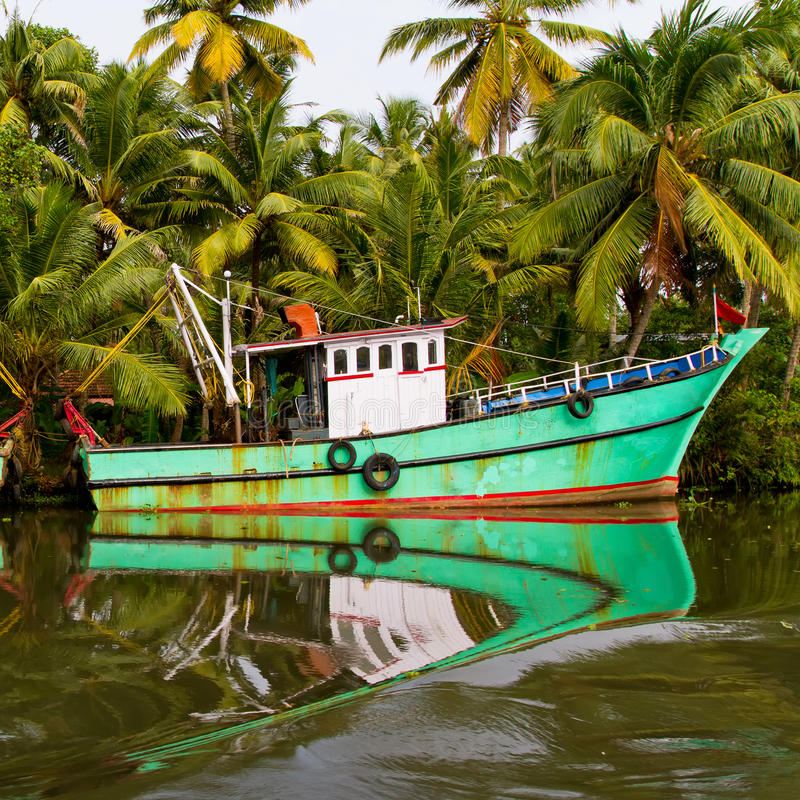Indian fishing-boat. With beautiful reflection in the water at famous backwaters of Kerala. Kochi, Kerala, India stock photography