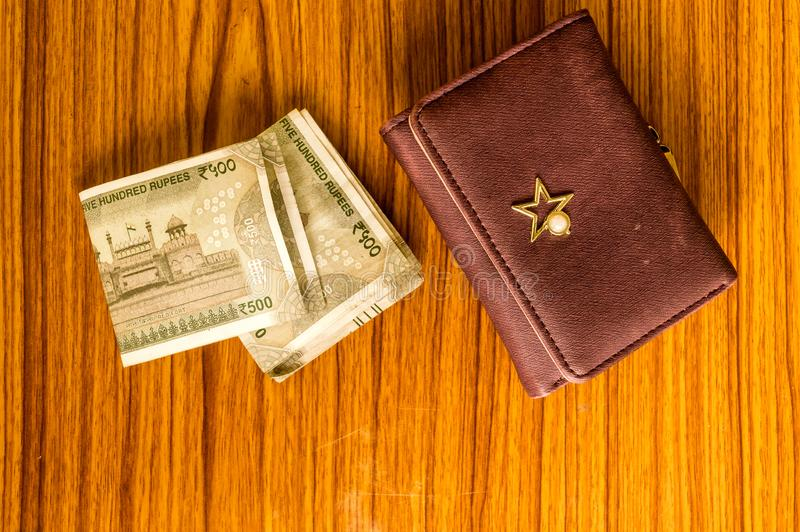 Indian five hundred 500 rupee cash note in brown color wallet leather purse on a wooden table. Business finance economy concept. High angel view with copy stock photo