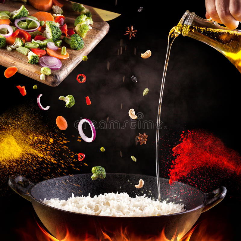 Indian food cooking. Indian vegetarian biryani with vegetables and spices in cooking process on black background stock photos