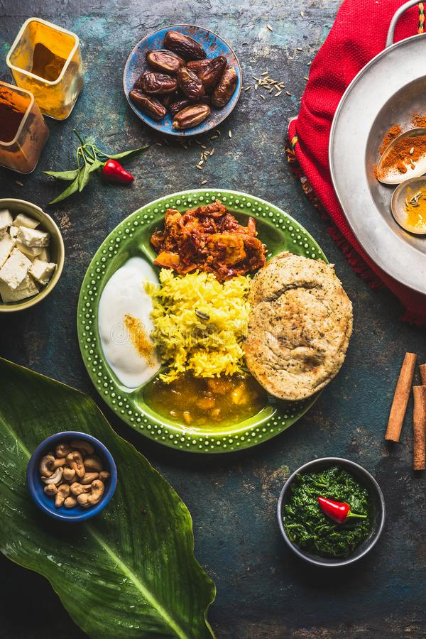 Indian food dish with paneer cheese , curries, rice, naan bread, samosas on dark rustic background stock photos