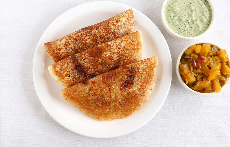 Indian Food Masala Dosa. Masala dosa, a traditional and popular South Indian vegetarian food, and coconut chutney and sweet pumpkin curry royalty free stock image