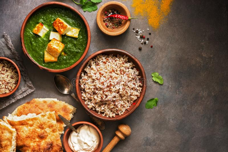 Indian food. Palak paneer or Spinach and Cottage cheese curry, rice, spices , naan, on a dark background. Top view, copy space royalty free stock image