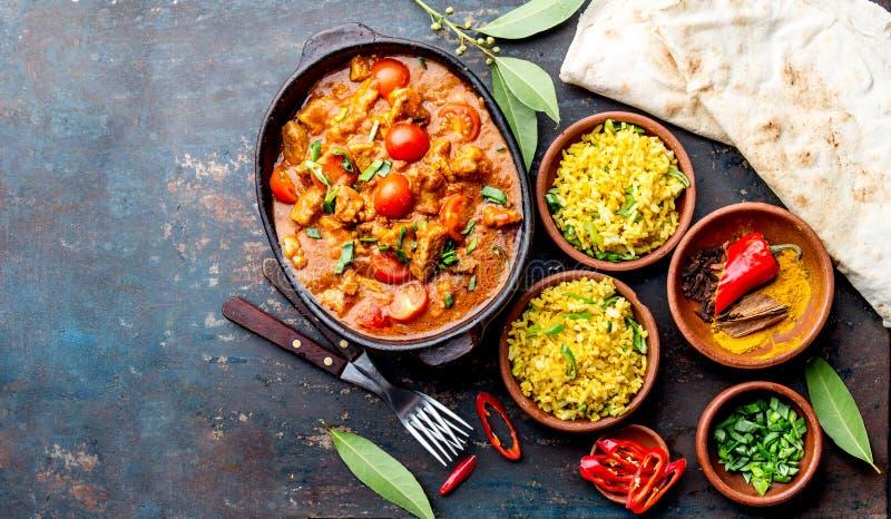 INDIAN FOOD. ROGAN JOSH curry sauce. Pork rogan josh with rice and naan bread royalty free stock photo