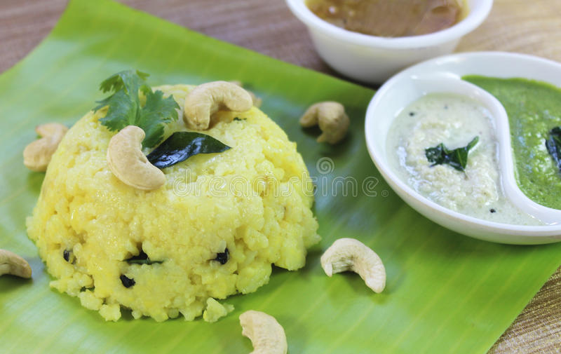 Indian food. South Indian food pongal on a banana leaf with side dish with wooden background stock photography