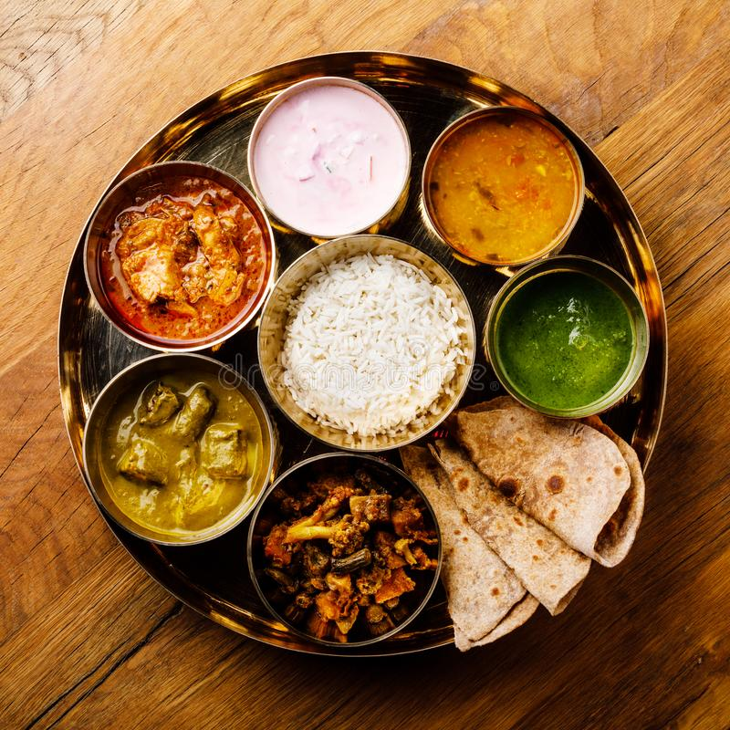 Indian food Thali Indian-style meal with chicken meat. On wooden table stock images