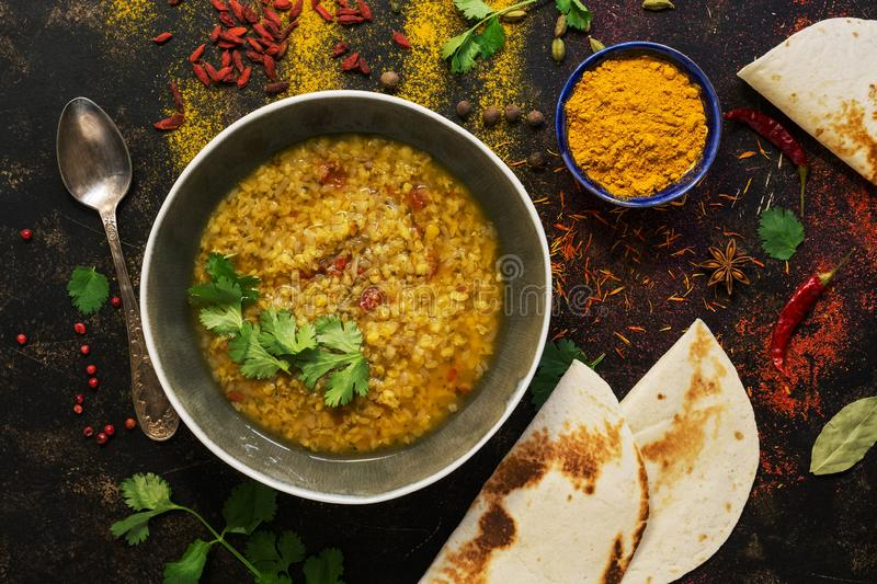 INDIAN FOOD. Thick Indian red lentil soup in the background with spices and homemade bread pita, lavash bread. View from above royalty free stock photos
