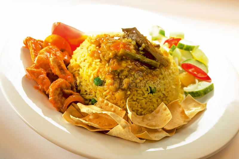 Indian fried rice. Frontal view of a plate of Indian fried rice with meat, mixed vegetables and flour crackers stock image
