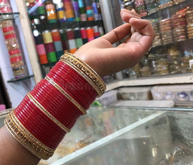 Indian girl in the bangle market. The girl is wearing the red bangles which she has shopped from the Indian bangle market. In the background all you can see is royalty free stock image