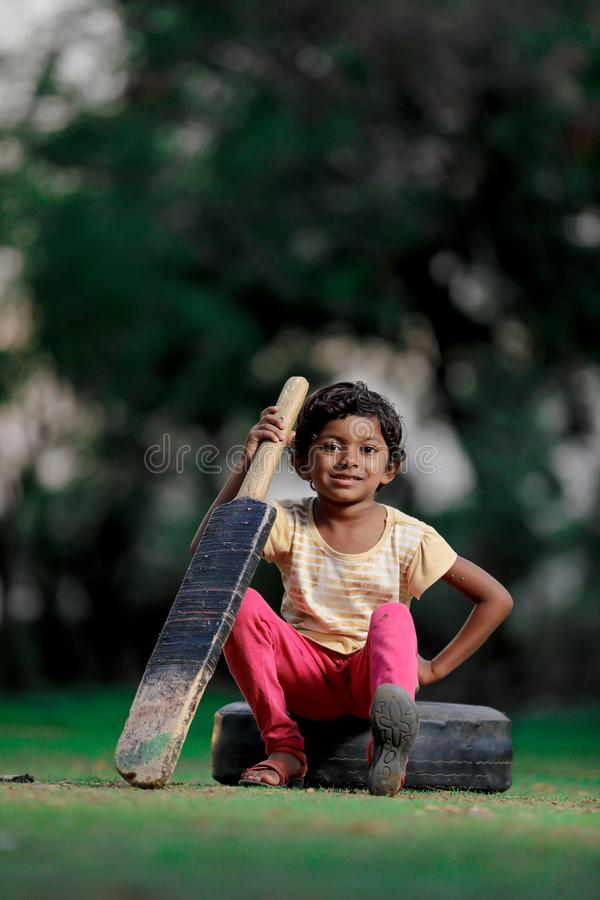 Indian girl child playing cricket royalty free stock photos