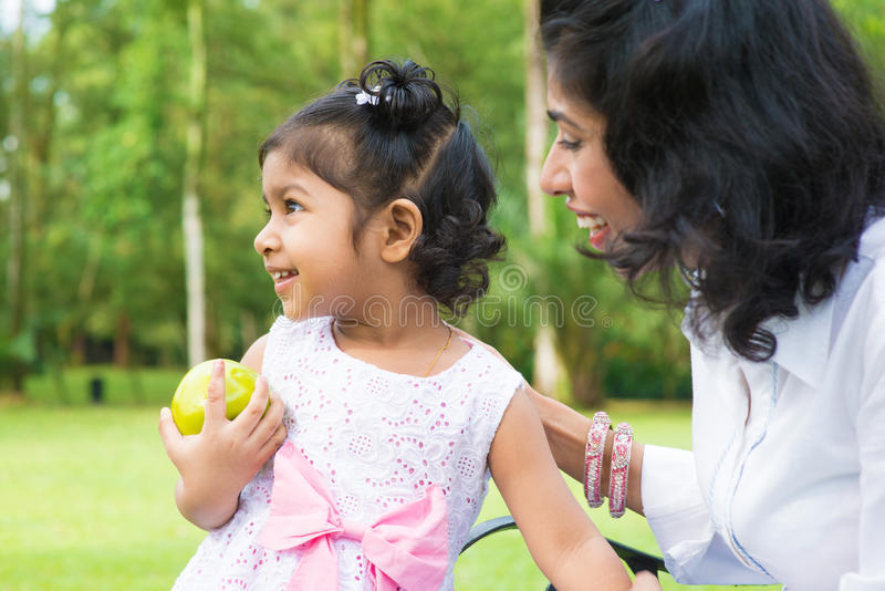 Indian girl holding an green apple outdoor stock image
