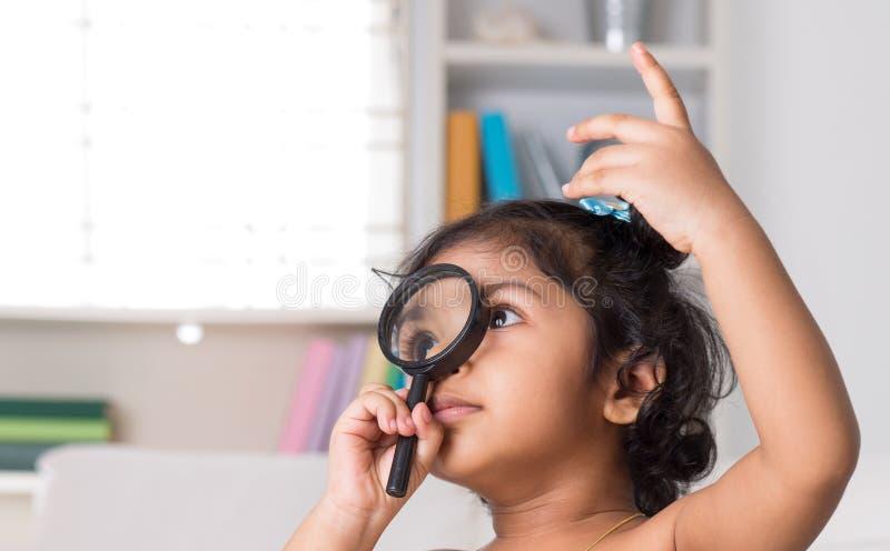 Indian girl peeking through magnifying glass. stock images