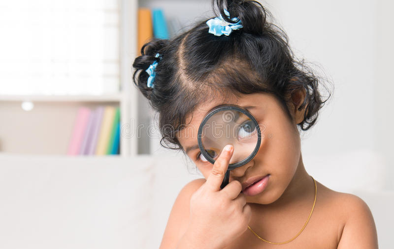 Indian girl peers at the camera through a magnifying glass. A little Indian girl peers at the camera through a magnifying glass, living lifestyle at home royalty free stock photo