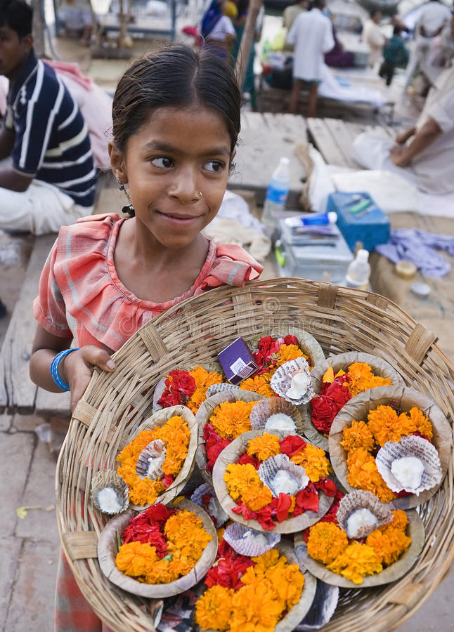 Indian girl selling offerings - Varanasi - India. A young Indian girl selling floral candles to float as offerings on the River Ganges in Varanasi in the Uttar stock photos