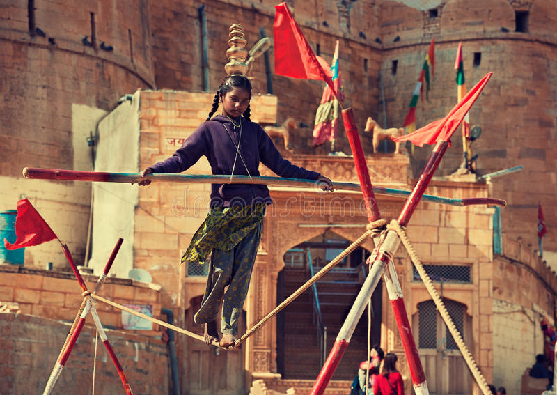 Indian girl tightrope walker at work. stock photos