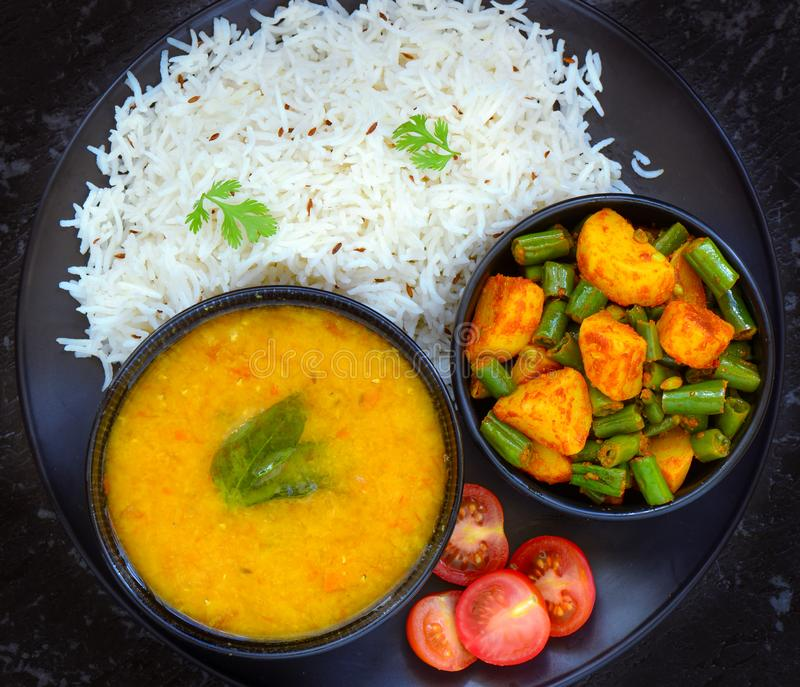 Indian glutenfree meal - Mung dal lentil,rice and beans curry. Indian gluten-free vegan meal -bowl of Moong dal lentil,rice and beans curry served with salad royalty free stock image