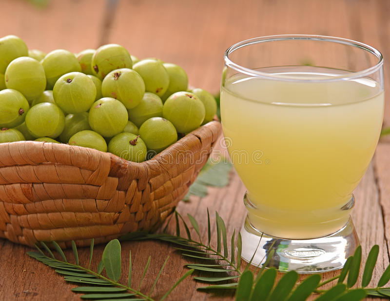 Indian gooseberry juice on wooden floor royalty free stock image