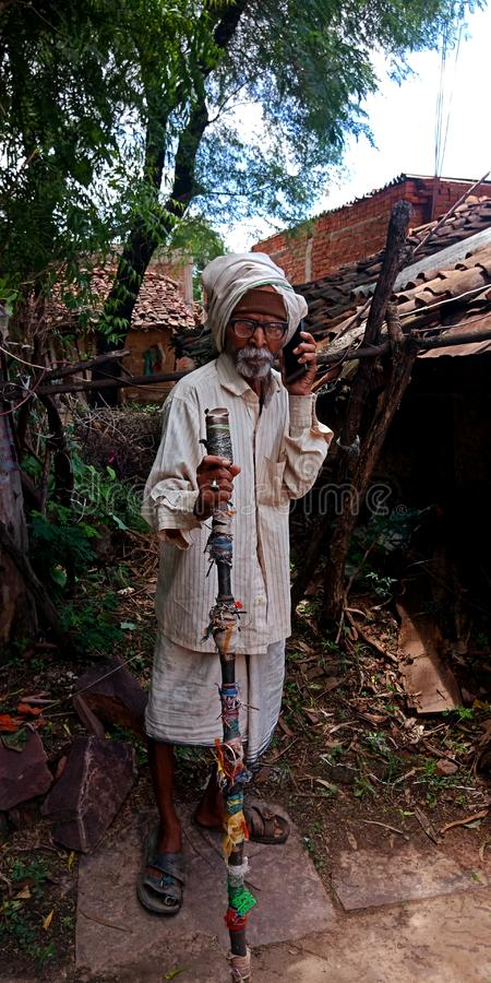 An indian grandfather using mobile during conversation. Matured, villager, learning, laptop, computer, system, illiterate, people, operating, seating stock image