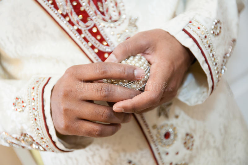 Indian groom holding ring stock photos