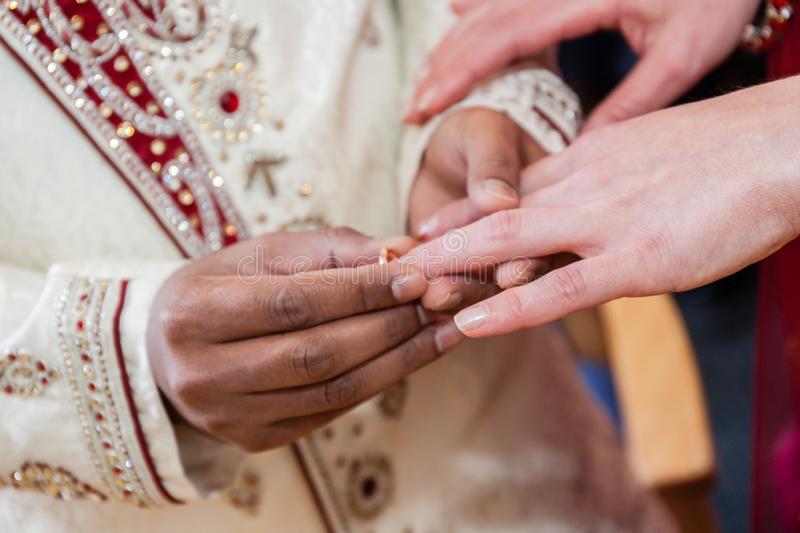 Indian groom putting ring on a bride`s hand stock photos