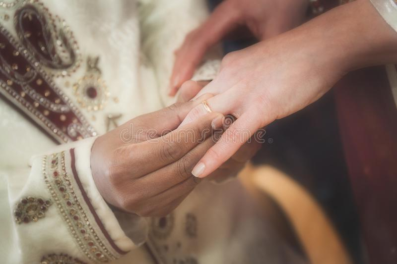 Indian groom putting ring on a bride`s hand royalty free stock photos