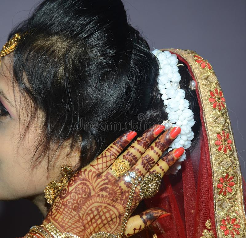 An Indian groom showing het beautiful white gajra, flowers on her head closeup shot stock photos