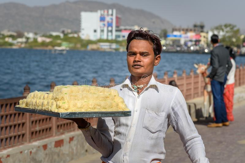 Indian guy carries sweets on tray for sale on the street in Ajmer. India. Ajmer, India - February 07, 2019: Indian guy carries sweets on tray for sale on the royalty free stock photo