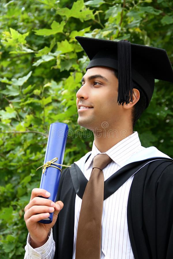 Indian guy in a graduation gown. stock images