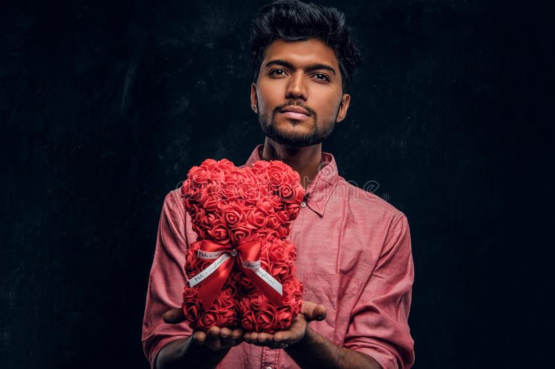Indian guy in a pink shirt holds a beautiful gift looking at the camera. Romantic mood, love relationship. A young Indian guy in a pink shirt holds a beautiful stock photos