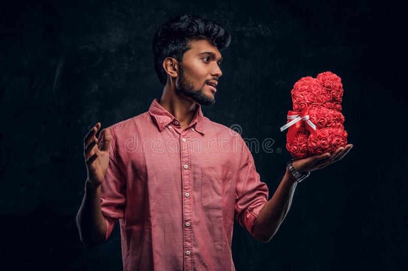 Indian guy in a pink shirt holds a beautiful gift and looks at him with an enthusiastic look. Romantic mood, love. A young Indian guy in a pink shirt holds a royalty free stock photography