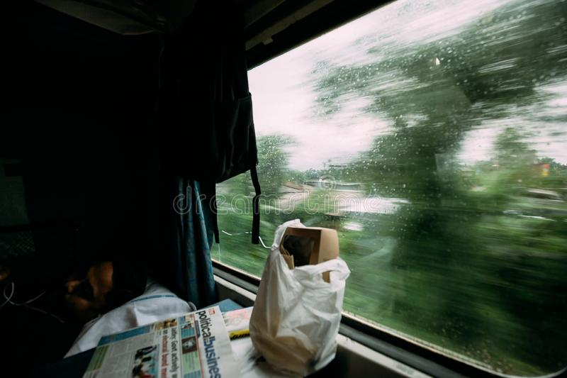An Indian guy sleeping with food and newspaper while a train moving with green tree motion blur in the outside. stock photography
