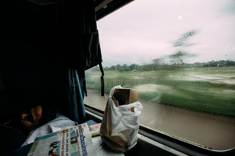 An Indian guy sleeping with food and newspaper while a train moving with green tree motion blur in the outside. royalty free stock photography