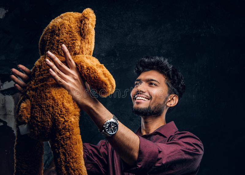 Indian guy in stylish shirt looks at his lovely teddy bear while holding it in hands. Studio photo against a dark. Young Indian guy in stylish shirt looks at his stock image