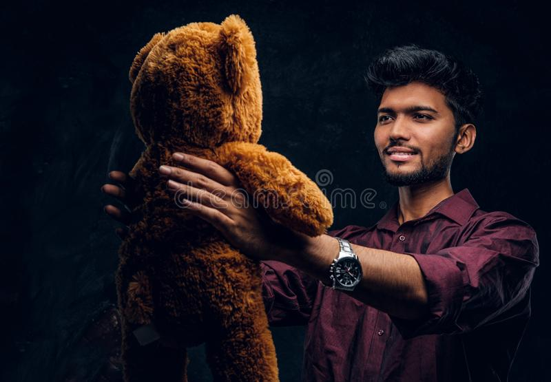 Indian guy in stylish shirt looks at his lovely teddy bear while holding it in hands. Studio photo against a dark. Young Indian guy in stylish shirt looks at his royalty free stock photo