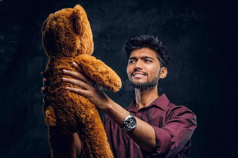 Indian guy in stylish shirt looks at his lovely teddy bear while holding it in hands. Studio photo against a dark. Young Indian guy in stylish shirt looks at his stock photography
