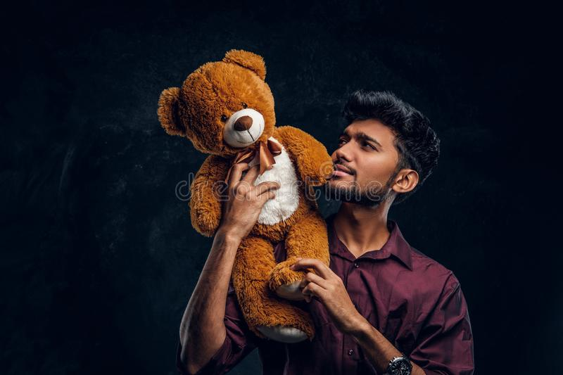 Indian guy in stylish shirt looks at his lovely teddy bear while holding it in hands. Studio photo against a dark. Young Indian guy in stylish shirt looks at his stock photos